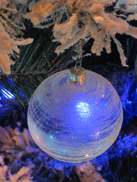 A frosted christmas ball with blue lights
