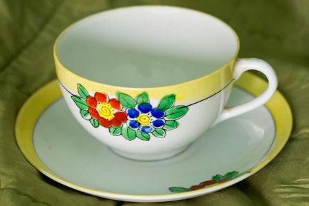 a 1930's tea cup in yellow and white with hand painted flowers