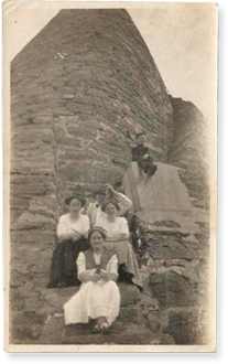 victorian ladies sitting at the bottom of a rock formation