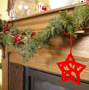 a felt star hanging from greenery at christmas in front of an antiqe oak mantle